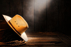 American West Rodeo Cowboy Straw Hat in Old Barn. American West rodeo cowboy traditional white straw hat on a wooden box with ranching rope in a smoky and dusty stock image