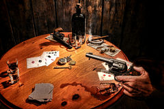 American West Saloon Gambler Holding Gun at Poker. American West Legend armed gambler bandit holding a revolver gun in his hand and threatening a cheater cowboy Stock Image