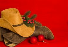 American West traditional boots and cowboy hat on christmas red. Background for text stock images