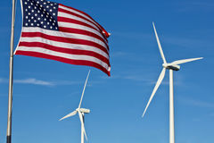 American Wind Power. An american flag flies in the foreground, with two wind power generator windmills turn in the background Stock Images