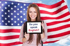 American Woman Asking Do You Speak English. Young Woman Holding Digital Tablet Asking Do You Speak English In Front Of Usa Flag Stock Images