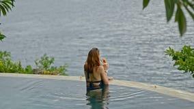 American woman drink cocktail having happy holiday in pool in Bali resort. stock video footage
