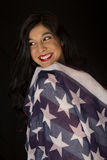 American woman with flag draped over her shoulder smiling Stock Photo