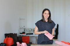 American woman making pink leather wallet at home atelier. American craftswoman making pink leather wallet at home atelier. Concept of home handicraft business Stock Photos
