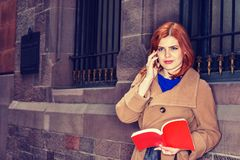 Young American Woman reading red book, talking on cell phone outdoor in New York. American Woman with red hair reading red book, talking on cell phone outside in Royalty Free Stock Image