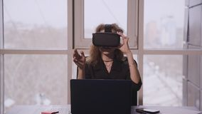 American woman wearing VR headset and working sitting front of laptop screen in office. American woman wearing VR headset and working sitting front of laptop stock footage