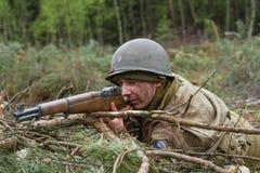 American World War II trooper during combat. American World War II infantry soldier prepering for shooting Royalty Free Stock Image