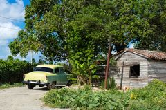 American yellow Chevrolet parked bevore a cuban old house in the suburb from Santa Clara Cuba - Serie Cuba Reportage.  Royalty Free Stock Image