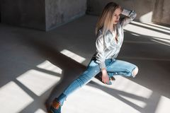 American young blonde woman in stylish shirt in vintage ripped jeans in trendy cowboy boots posing sitting indoors with sunlight. Sexy beautiful fashion model royalty free stock images
