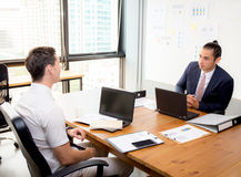 American young businessmen interacting and talking teamwork. American young businessmen interacting and talking teamwork at meeting in office Royalty Free Stock Image