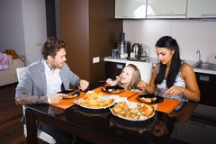 American young family eating pizza stock images