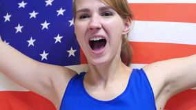 American Young Woman Celebrating while holding the flag of America in Slow Motion royalty free stock images