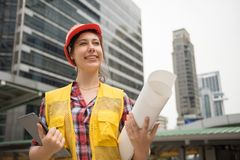 American young woman engineer in city. Portrait of Beautiful American young woman engineer with orange helmet hat engineer paper blueprint, digital tablet at Stock Photo