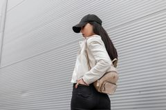 American young woman in a stylish cap with a trendy gold backpack in a vintage white leather jacket traveling along the street. Near the metal wall. Attractive stock photos