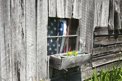 Americana. American flag in the window of an old rural rustic wooden barn, Fourth Of July Stock Image