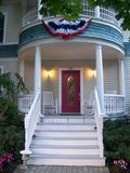 Americana Front Porch. A beautiful font porch with rockers to welcome you shows it's patriotic colors for the touch of americana and pride Royalty Free Stock Photo