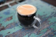 Americano caliente de la taza en la madera Imagen de archivo libre de regalías