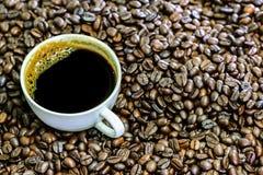 Americano chaud, café noir dans la tasse blanche avec des grains de café Image libre de droits