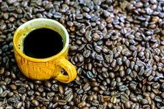 Americano chaud, café noir dans la tasse jaune avec des grains de café Photographie stock libre de droits