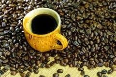 Americano chaud, café noir dans la tasse jaune avec des grains de café sur le backgrond de sac Photo stock