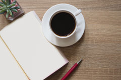 Americano coffee, note books, and pen on table. Americano coffee, note books, and pen are placed on a brown table wooden workspace Stock Image