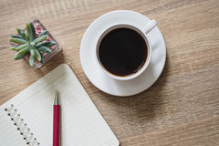 Americano coffee, note books, and pen on table. Americano coffee, note books, and pen are placed on a brown table wooden workspace Royalty Free Stock Photos