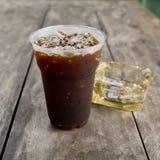 Americano délicieux de café de glace avec la cigarette sur le vieil en bois Photographie stock