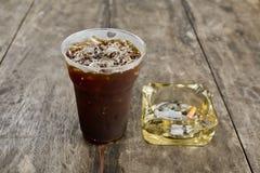 Americano délicieux de café de glace avec la cigarette sur le vieil en bois Images libres de droits