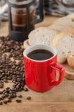 Americano dans la tasse rouge avec des grains de café sur le fond en bois Images stock
