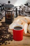 Americano dans la tasse rouge avec des grains de café sur le fond en bois Photographie stock libre de droits