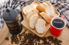 Americano dans la tasse rouge avec des grains de café sur le fond en bois Images libres de droits