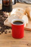 Americano dans la tasse rouge avec des grains de café sur le fond en bois Photo libre de droits