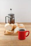 Americano dans la tasse rouge avec du pain coupé en tranches sur le fond en bois Photo stock