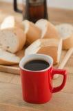 Americano dans la tasse rouge avec du pain coupé en tranches sur le fond en bois Image libre de droits