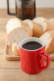Americano dans la tasse rouge avec du pain coupé en tranches sur le fond en bois Images libres de droits