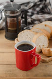 Americano dans la tasse rouge avec du pain coupé en tranches sur le fond en bois Images stock