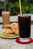 Americano de café de glace avec le biscuit de riz (Khao Tan) Images stock