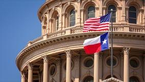 Americano e Texas Flags Flying em Texas State Capitol Building em Austin Imagem de Stock