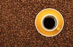 Americano-Gelbtasse und untertasse auf Kaffeebohnen Stockbilder