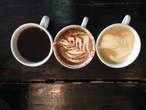 Americano, moka et latte chauds sur la table en bois de brun foncé Photographie stock