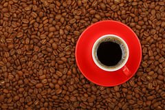 Americano in red cup with saucer on coffee beans Stock Images