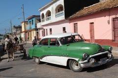 Americano viejo y un carro en Trinidad Imágenes de archivo libres de regalías