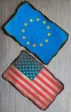 Americano y europeo señala el fondo por medio de una bandera Fotos de archivo libres de regalías