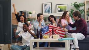 Americanos emocionados con las banderas que miran fútbol en la TV en casa que celebran la victoria metrajes