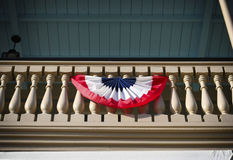 Americans celebrate!. Celebratory red white blue flag displayed on a balcony Royalty Free Stock Image