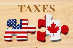 Americans paying Canadian taxes with tax treaty. Americans paying Canadian taxes, Two puzzle pieces with the flags of USA and Canada on wood with text Taxes royalty free stock images