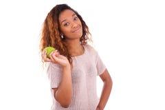 非洲人拿着一个绿色苹果的Americanyoung妇女 免版税库存图片