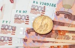 Amerikaans dollarmuntstuk over Russische bankbiljetten Stock Foto