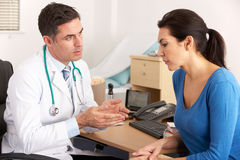 Amerikaanse arts die aan vrouw in chirurgie spreekt Royalty-vrije Stock Foto's