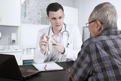 Amerikaanse arts die geneeskunde voor zijn patiënt verklaren Stock Afbeeldingen